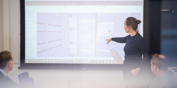 Dame som peker på stor skjerm